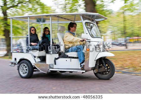 Solar powered tuc tuc driving on a road - stock photo