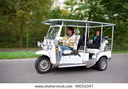 Solar powered tuc tuc driving on a road, with two female passengers in the back - stock photo