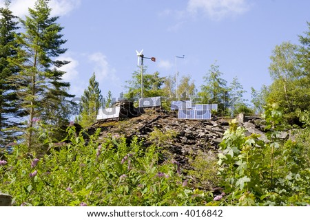solar PV cells and wind turbines high on the hill. - stock photo