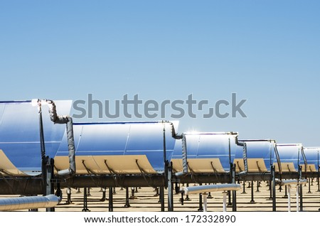 solar thermal electric generating plant collection mirrors with blue sky  - stock photo