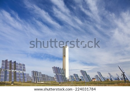 Solar tower surrounded by mirror panels harnessing the sun's rays to provide alternative renewable green energy. Situated in Adalucia, Spain, just outside Seville. - stock photo