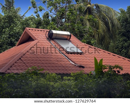 Solar water heater sits on the roof of a home in the Maldive islands - stock photo