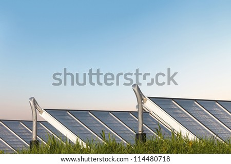 Solar water heating system on grass with an orange blue sky in the background - stock photo