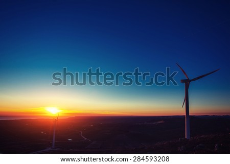 Solar wind turbines at sunset. - stock photo