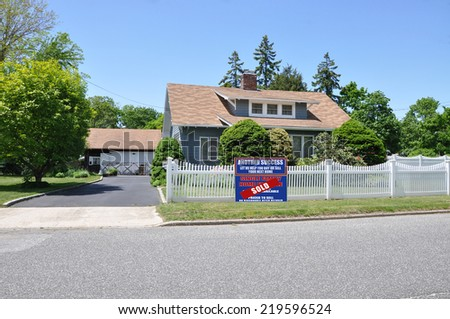 Sold (Another success let us help you buy sell your next home) real estate sign on front yard lawn of suburban cape cod style home with white picket fence clear blue sky USA residential neighborhood - stock photo