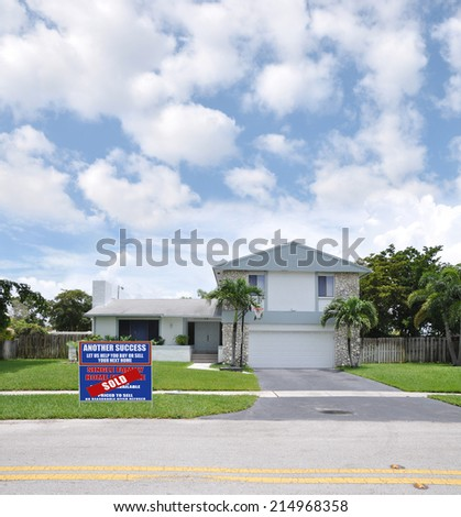 Sold (Another Success let us help you buy sell your next home) Real Estate Sign on front yard of Suburban Back Split style home residential neighborhood USA blue sky clouds
