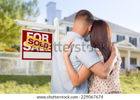 Sold For Sale Real Estate Sign and Affectionate Military Couple Looking at Nice New House. - stock photo