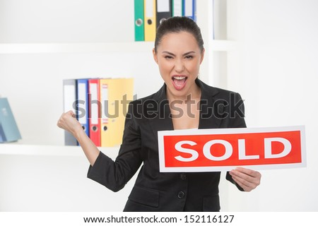 Sold! Happy young woman in formalwear holding a sold sign