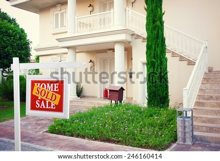 Sold home for sale Real estate sign in front of new house - stock photo
