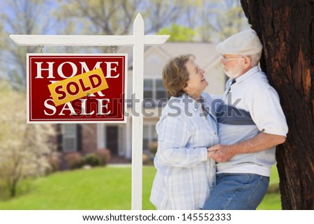 Sold Home For Sale Real Estate Sign with Happy Affectionate Senior Couple Hugging in Front of House.