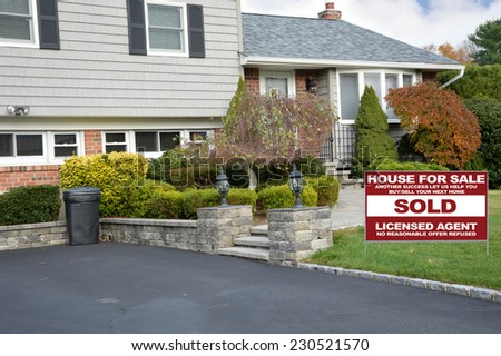 Sold Real Estate (another success let us help you buy sell your next home) sign on front yard lawn of suburban high ranch style home residential neighborhood USA