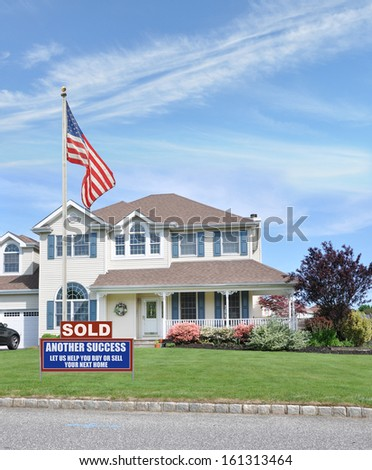 Sold Real Estate Sign Another Success Let Us Help You Buy Sell your Next Home American Flag Suburban McMansion style Home Landscaped Front Yard Lawn Residential Neighborhood USA Blue Sky Clouds - stock photo