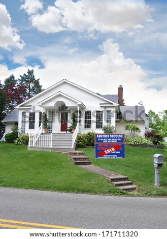 Sold real estate sign (another success let us help you buy sell your next home) suburban home residential neighborhood USA blue sky clouds - stock photo