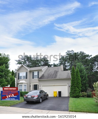 Sold Real Estate Sign Front Yard Lawn Suburban Home with Parked Automobile Two Car Garage Yellow Trash Can Daytime Blue Sky Clouds Residential Neighborhood USA - stock photo