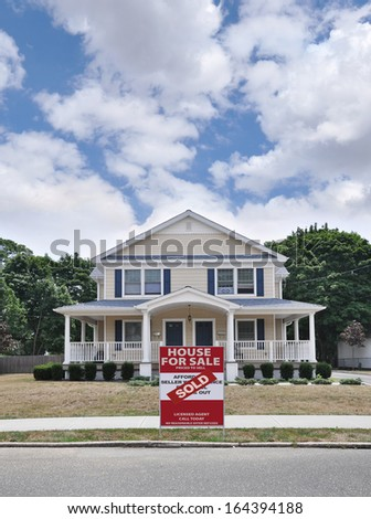 Sold Real Estate Sign Large Suburban Two Family Home Blue Sky Clouds USA Residential Neighborhood Street - stock photo