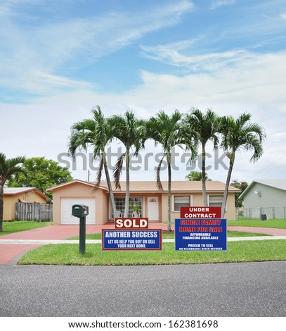Sold Under Contract Real Estate Sign front yard lawn suburban ranch style home with palm trees Residential Neighborhood USA Blue Sky Clouds - stock photo
