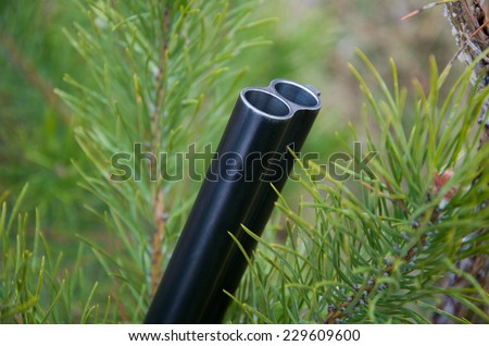Solder the barrels of the shotgun on the background of green tree - stock photo