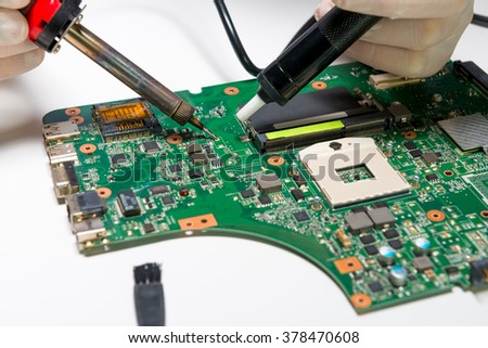 Soldering a computer board - stock photo
