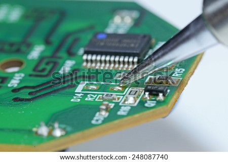 Soldering a microchip - stock photo