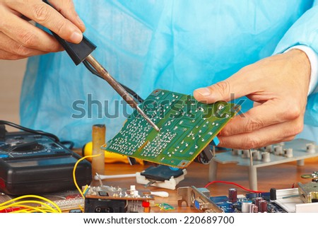 Soldering electronic board in the service workshop - stock photo