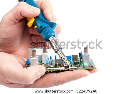 Soldering iron in hand and electric board isolated on a white background. - stock photo