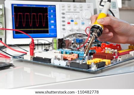 Soldering of electronic equipment - stock photo