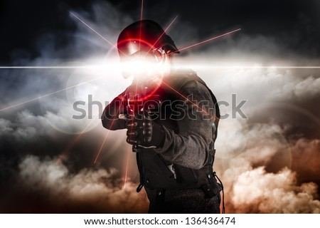 Soldier aiming assault rifle laser sight - stock photo