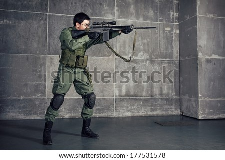 Soldier aiming the target with gun in building - stock photo