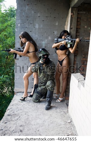 Soldier and two naked women with rifles