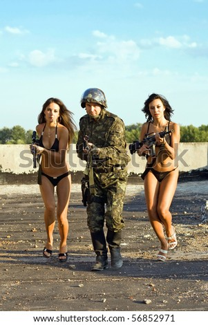Soldier and two women in underclothes with rifles running on the roof - stock photo