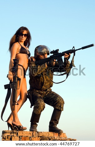 Soldier and woman in bikini staying on the brick wall