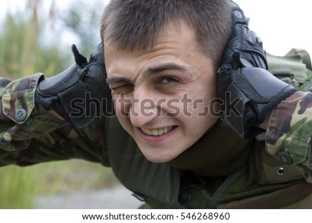 Soldier at the knees. Man covers his ears from the explosion. Hands covering her ears, a loud explosion. Portrait of a soldier covering his ears and bares his teeth standing over background of nature.