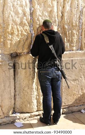 Soldier at the wailing western wall,  Jerusalem, Israel - stock photo
