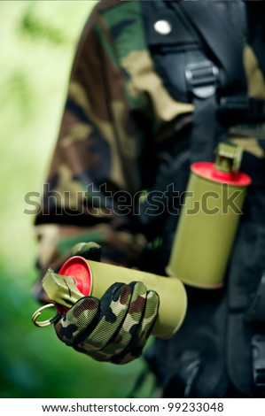 soldier carrying smoke bomb - stock photo