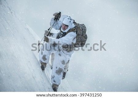 Soldier climbs the mountain. Military dressed in camouflage against the background of a winter landscape - stock photo