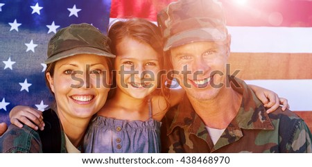 Soldier couple reunited with their daughter in front of american flag - stock photo