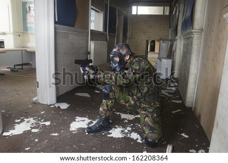 soldier crouching in a hallway and pointing a gun into a room of an abandoned building