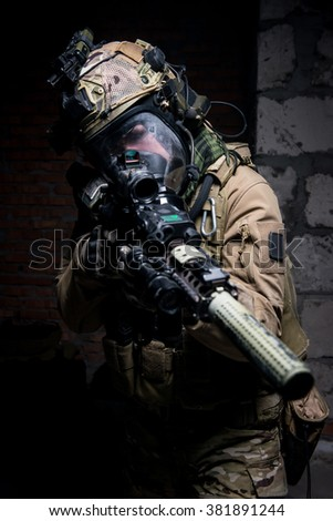 Soldier dressed in protective equipment as helmet and gas mask aiming at target from assault rifle/Soldier dressed in protective equipment, aiming at target.Selective focus. - stock photo