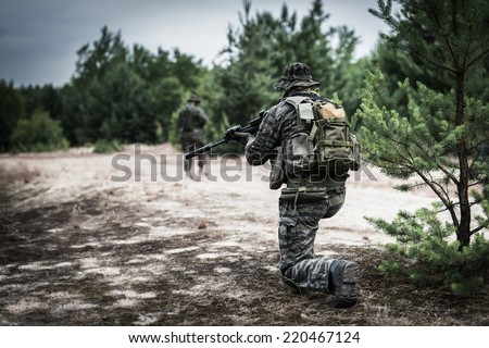 Soldier dressed in tiger stripe camouflage, securing area - stock photo