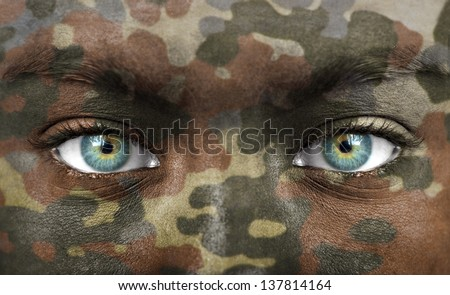 Soldier face with camo colours - stock photo