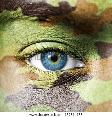 Soldier face with camo texture macro - stock photo