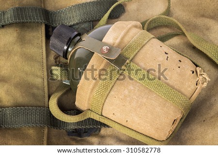 Soldier flask (canteen) in decay cloth winding on rucksack - stock photo