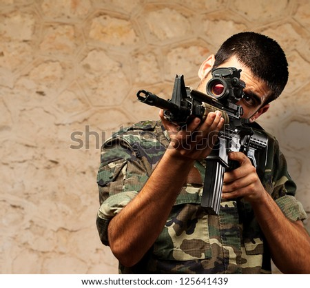 Soldier Gunman Aiming His Target against a brown rock Background