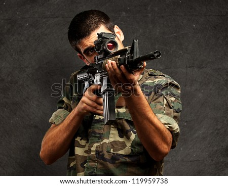 Soldier Gunman Aiming His Target against a grunge wall Background - stock photo