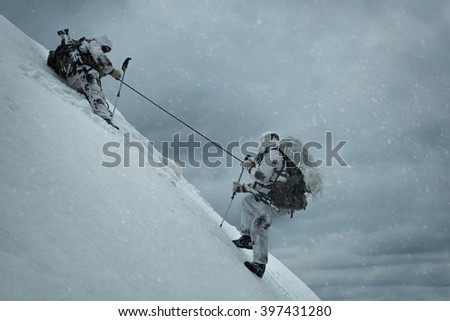 Soldier helping another to climb up the hill. Two military men in the background of a winter landscape - stock photo