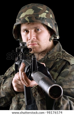 Soldier holding a gun in studio. Isolated - stock photo