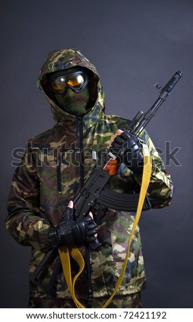 Soldier holding a machine gun AK-47 - stock photo