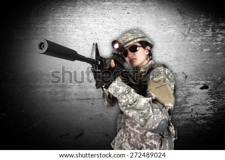 soldier holding his assault rifle isolation on gray - stock photo