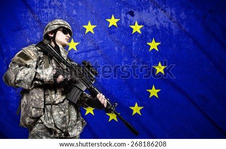 soldier holding rifle on a European Union flag background - stock photo