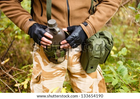 Soldier in a forest with flask. - stock photo